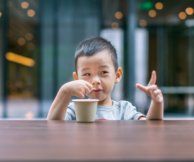 Cheeky toddler with milk moustache sitting with a cup at an outdoor table.