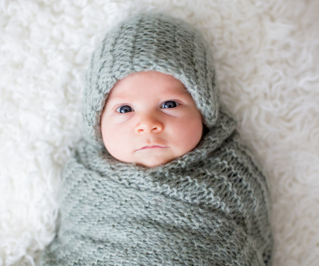 Newborn infant wrapped in a knitted throw