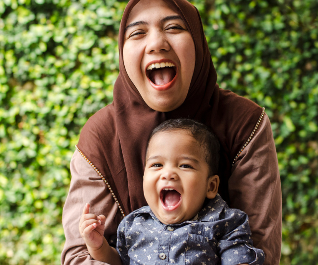 Smiling woman wearing hijab nursing an adorable smiling infant boy with a green foliage wall behind them.