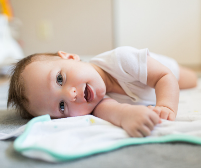 Smiling baby laying a on a bed in a sun filled room.