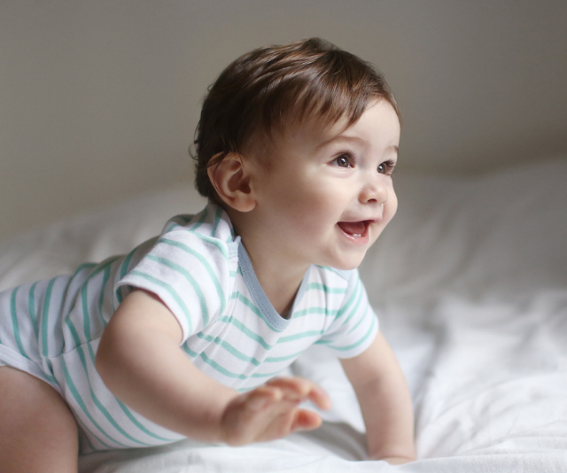 Cheeky baby in a blue and white striped onesie crawling across a bed in a sun-filled room.