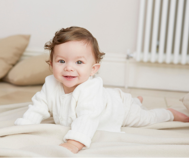 Cute curly haired baby doing tummy time on a floor rug.