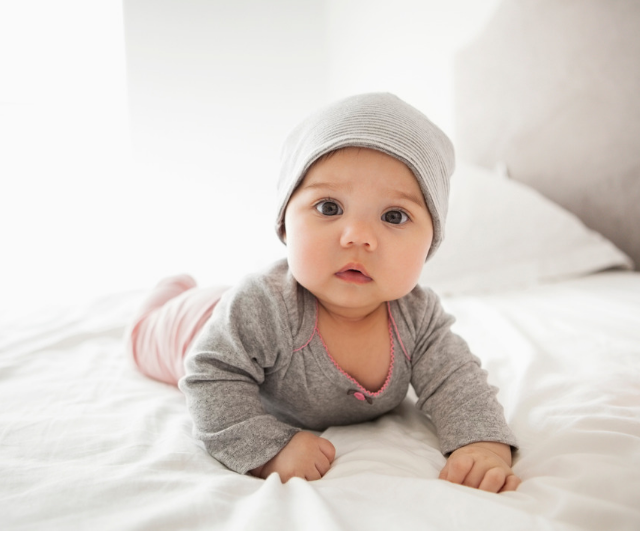 Adorable chubby cheeked baby doing tummy time on bed with white linen while wearing a grey knit onesie and beanie style hat while sun streams in the window.
