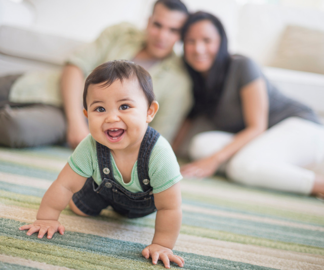 Baby boy crawling across rug with parents laughing in the background.