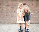 three smiling children in school uniform in front of a brick wall
